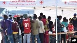 Les migrants s'alignent devant une tente de la Croix-Rouge après avoir débarqué du navire irlandais Marine LE Niamh au port de Messine, en Sicile, Italie, 24 août 2015. (AP Photo / Carmelo Imbesi)