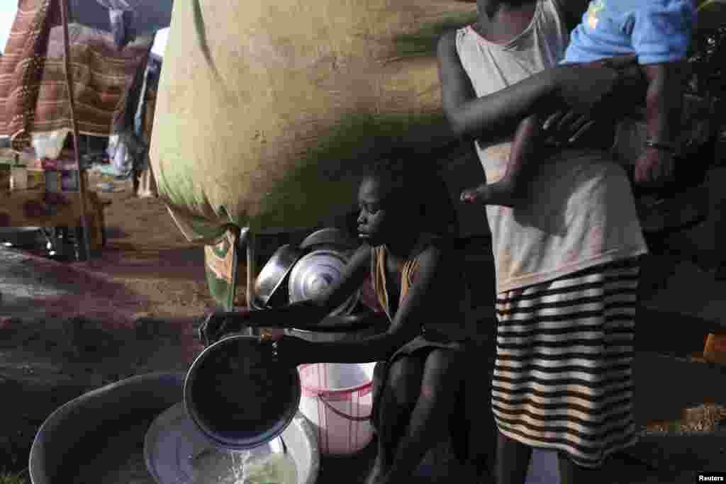 Uma menina sul-sudanesa lava pratos no campo de refugiados da UNMISS em Tongping, Juba, Sudão do Sul, Fev. 19, 2014.