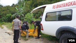 Evakuasi jenazah terduga teroris Basir alias Romzi untuk dipindahkan ke mobil ambulans Rumah Sakit Bhayangkara Polda Sulawesi Tengah, Senin (4/3) (Foto: VOA/Yoanes Litha)
