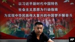 一个行人路过北京街头宣传习近平中国梦的宣传广告牌。