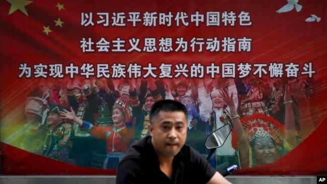 一个行人路过北京街头宣传习近平中国梦的宣传广告牌。(2020年9月11日)