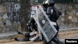 Policías venezolanos reprimen una protesta popular y se llevan detenido a un manifestante.