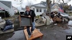 Một cư dân New York đang dọn dẹp nhà cửa, mang vứt bỏ những đồ đạc bị hư hại sau trận lụt do bão Sandy gây ra