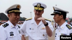 Robert L. Thomas Jr. (C), Commander of the U.S. Seventh Fleet talks with Chinese general Yuan Yubo (L) at a port in Qingdao, during the U.S. Seventh Fleet Flagship USS Blue Ridge visit to Shandong province, China, Aug. 5, 2014.