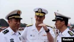 """美国第七舰队司令小罗伯特•L•托马斯中将在舰队旗舰""""蓝岭号""""访问青岛期间与中国北海舰队司令袁誉柏少将(左)交谈。(2014年8月5日)"""