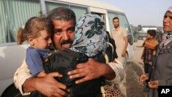 一名伊拉克士兵与他逃离伊斯兰国控制城镇的家人团聚