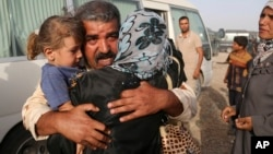 Abdul Rahman Ismail, an Iraqi soldier who has been targeted by Islamic State extremists who destroyed his house two years ago, is reunited with his family after they were able to flee their Islamic State held town, as displaced Iraqi families gather outside. (AP)