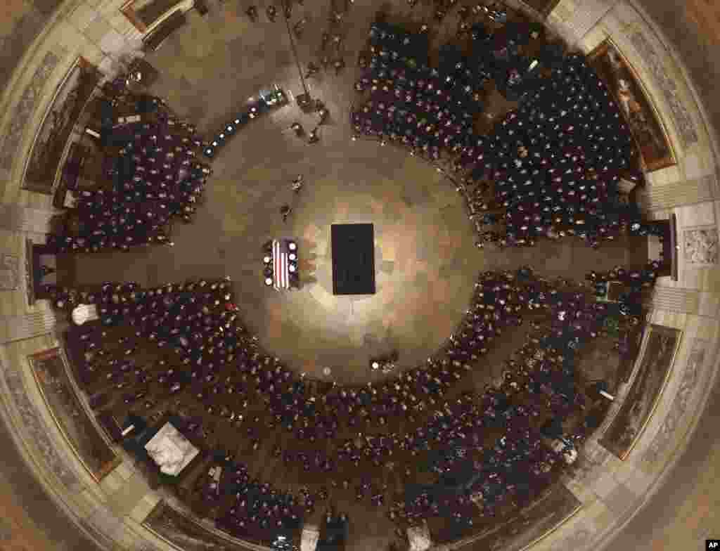 The flag-draped casket of former President George H.W. Bush is carried by a joint services military honor guard into the U.S. Capitol Rotunda, Dec. 3, 2018, in Washington.