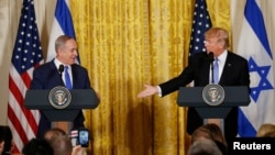 FILE - U.S. President Donald Trump, right, reaches out to Israeli Prime Minister Benjamin Netanyahu during a joint news conference at the White House in Washington, Feb. 15, 2017.