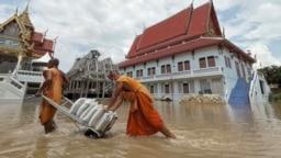Dua biksu Buddha menarik kereta yang mengangkut karung-karung pasir untuk melindungi kuil mereka dari banjir di provinsi Ayutthaya, Thailand (Foto: Dailynews via Reuters).
