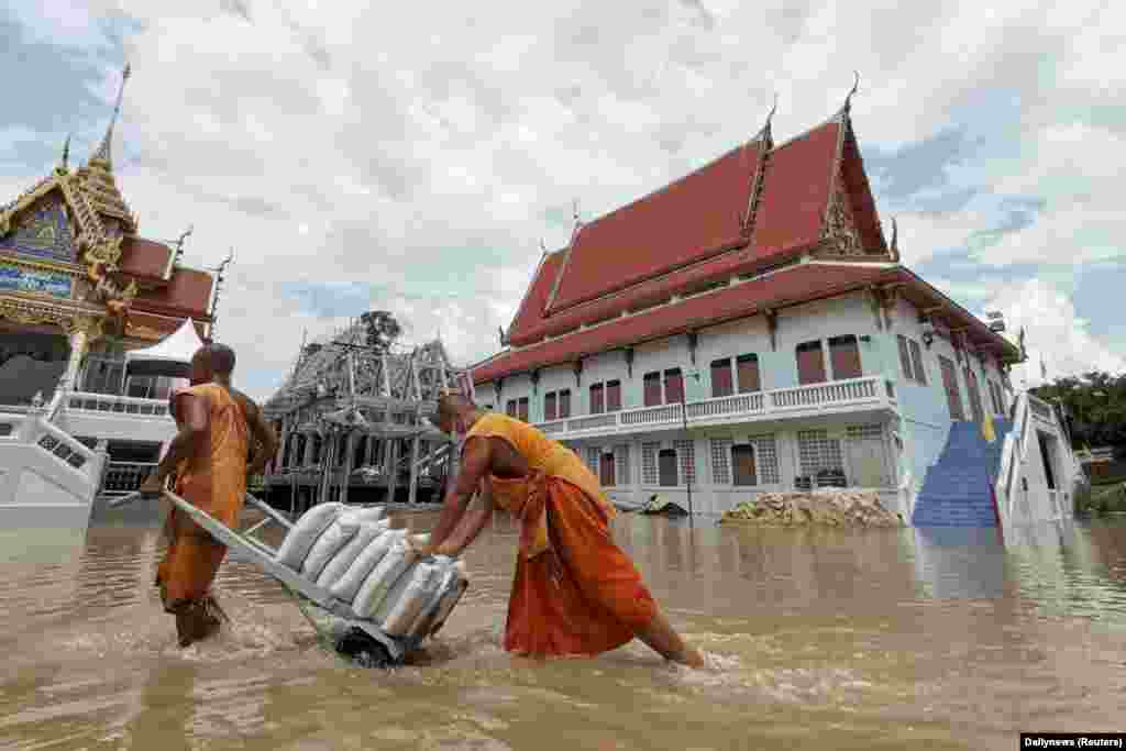 Buddhist monks pull a cart carrying sandbags to protect a temple from a flood in Ayutthaya province, Thailand.