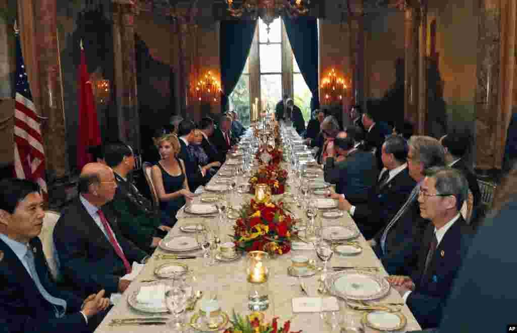 美国总统川普和家人、高级顾问同中国国家主席习近平和随行人员在佛罗里达州海湖庄园的晚宴上(2017年4月6日)。从图片上看,两位元首在交谈,库什纳和彭丽媛在交谈,伊万卡和房峰辉在交谈,而王毅和班农在注视两位元首。