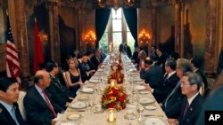 President Donald Trump and Chinese President Xi Jinping, with their wives, first lady Melania Trump and Chinese first lady Peng Liyuan are seated at the center, during a dinner at Mar-a-Lago in Palm Beach, Florida, April 6, 2017.