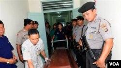 Petugas kepolisian mengawal peti jenasah tersangka teroris yang tertembak mati ke rumah sakit di Denpasar, Bali (19/3).