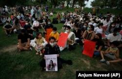 """Seorang aktivis hak-hak perempuan meletakkan lilin di samping poster bergambar Noor Mukadam, yang baru-baru ini dipenggal, untuk memberi penghormatan kepada Noor dan korban kekerasan dalam rumah tangga lainnya, di Islamabad, Pakistan. (Foto: AP)"
