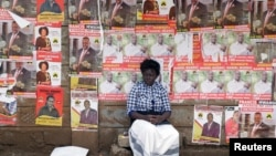 FILE - A woman sits in front of campaign posters in Nairobi, Kenya, April 26, 2017.