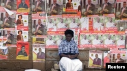 FILE - A woman sits in front of campaign posters as she waits to cast her ballot, during the Jubilee Party primary elections, at a polling centre in Nairobi, Kenya.