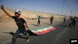 在打击库尔德武装人员的行动中,伊拉克军队10月16日向基尔库克中心推进。图中伊拉克男孩拖着一面库尔德旗子。