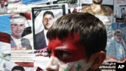 An anti-government protester, with his face painted in the colors of Yemen's and Syria's national flags, walks past pictures of people killed in anti-government clashes, during a rally demanding the ouster of Yemeni President Ali Abdullah Saleh, in Sanaa,