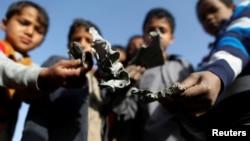 Anak-anak Yaman menunjukkan serpihan misil pasca serangan udara koalisi pimpinan Saudi di Sanaa, Yaman bulan lalu (20/1).