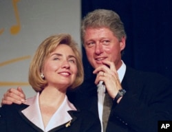 In this June 22, 1994 file photo, President Bill Clinton and first lady Hillary Clinton wait to address a group of young Democratic supporters known as the Saxophone Club in Washington.