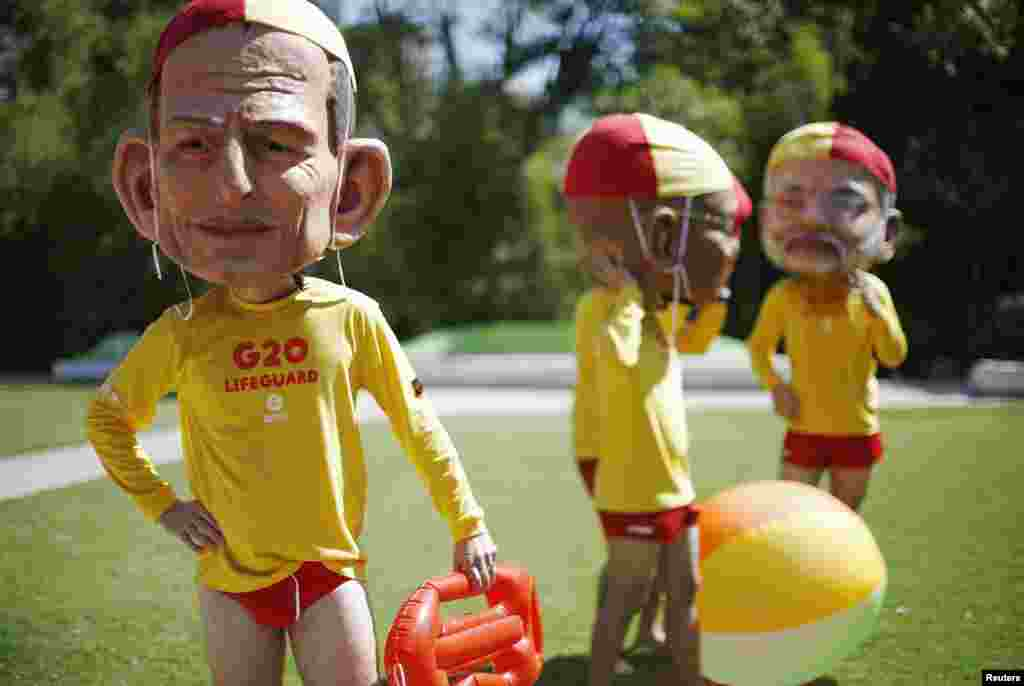 A protester, wearing a mask depicting Australian Prime Minister Tony Abbott and dressed as a lifeguard, calls for global equality among nations outside the venue site of the annual G20 leaders summit in Brisbane. Leaders depicted are (L-R) Australian Prime Minister Tony Abbott, South African President Jacob Zuma and Indian Prime Minister Narendra Modi.