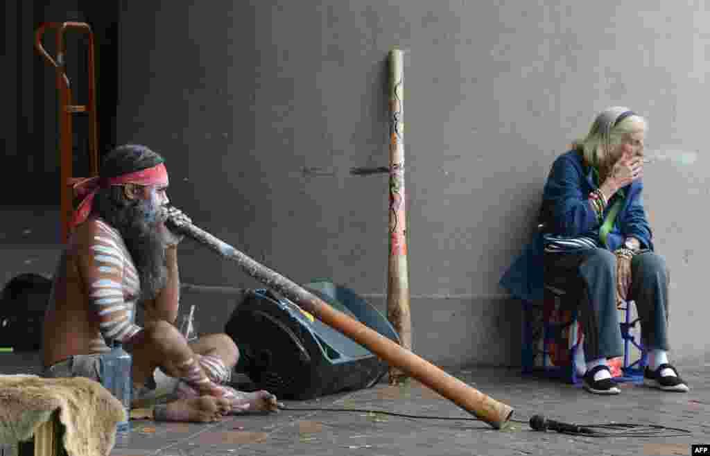 ស្ត្រីចំណាស់ម្នាក់ជក់បារី នៅពេលដែលបុរសអំបូរ Aboriginal ម្នាក់លេងឧបករណ៍តន្ត្រីម្យ៉ាងដែលគេហៅថា didgeridoo នៅផែ Circular Quay ក្នុងក្រុងស៊ីដនី ប្រទេសអូស្ត្រាលី។