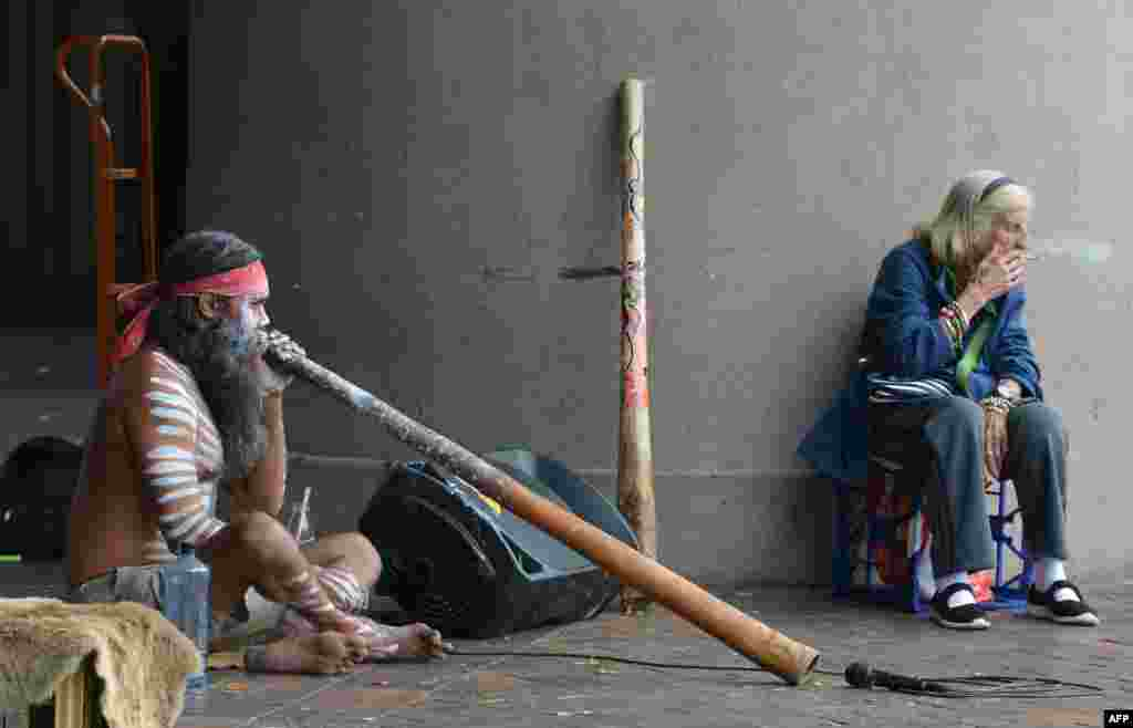 An elderly woman smokes a cigarette while an Aboriginal man plays a didgeridoo in Circular Quay in Sydney, Australia.