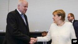 난민정책 해법을 놓고 마찰을 빚었던 앙겔라 메르켈 독일 총리(오른쪽)와 호르스트 제호퍼 내무장관이 독일 베를린의 의회에서 만나 악수하고 있다.