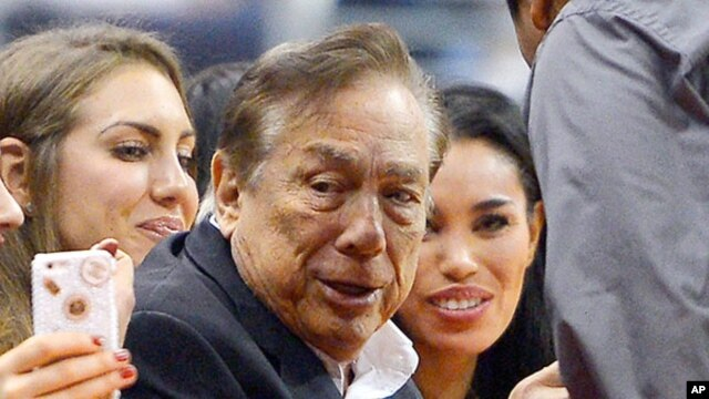 FILE - Los Angeles Clippers owner Donald Sterling, center, and V. Stiviano, right, watch the Clippers play the Sacramento Kings.