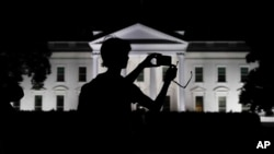 FILE - A tourist takes a photo from Pennsylvania Avenue of an illuminated White House in Washington, Aug. 25, 2017.