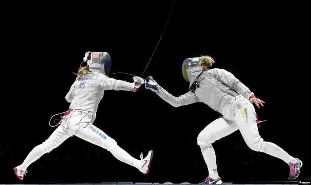 Russia's Ekaterina Dyachenko (L) competes against Ukraine's Olga Kharlan during their women's team saber final at the World Fencing Championships in Moscow.