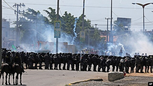 Riot police take position and fire tear gas at protesters gathering near Castelao stadium in Fortaleza, Brazil, June 19, 2013.