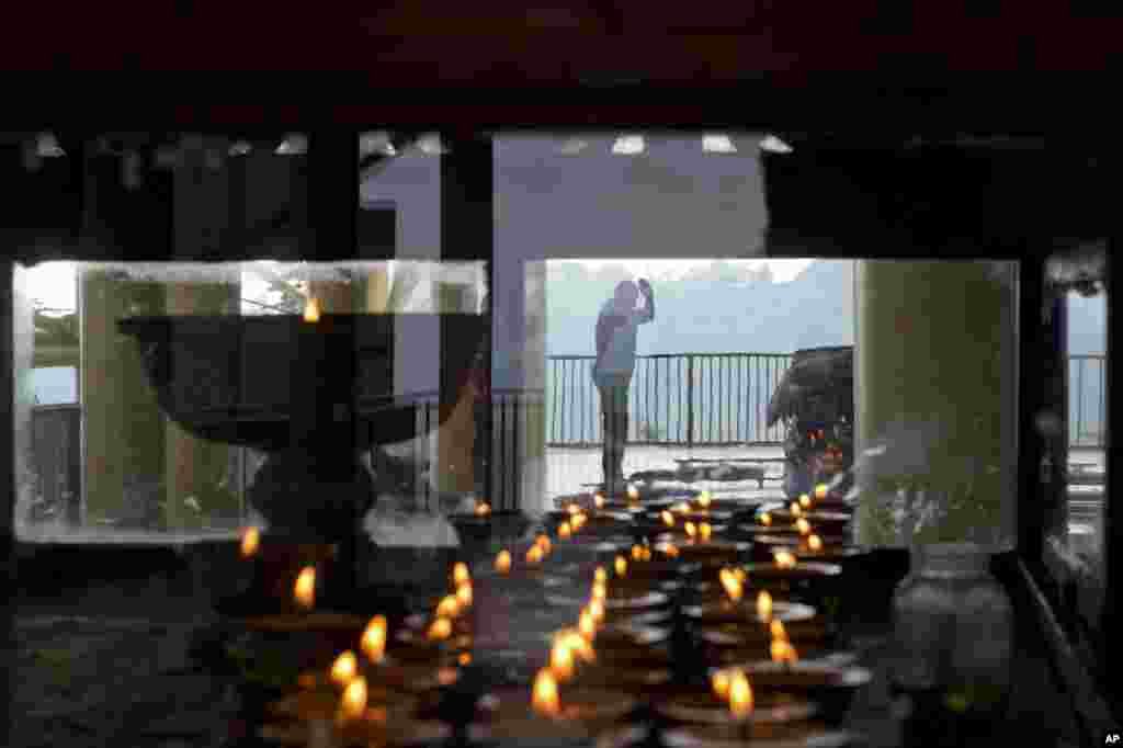 An exile Tibetan prays next to a glass enclosure containing traditional butter lamps at the Tsuglakhang temple in Dharmsala, India. The Dalai Lama, 80, remains at the Mayo Clinic in Rochester after cancelling his U.S. appearances for the month of October after doctors advised him to rest.