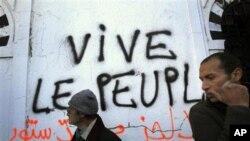 """抗议者在突尼斯市的墙上书写""""人民万岁"""""""