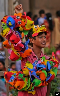 An Indian boy sells masks for children at a street in Hyderabad, India, June 11, 2016. Child labor remains widespread in India, despite the country's rapid economic growth over the past decade.