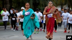 Middle-aged women in traditional Indian attire run along with youngsters during a 5-kilometer run, organized to celebrate International Women's Day in Bangalore, India, March 8, 2015.