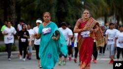 """Dua orang perempuan tengah baya mengenakan pakaian tradisional India mengikuti lari lima kilometer untuk memperingati Hari Perempuan Internasional di Banglore, India (8/3). Jaringan televisi India, NDTV, melancarkan protes siaran bisu, setelah pemerintah melarang stasiun televisi itu menayangkan film """"India's Daughter"""", Minggu malam (8/3)."""
