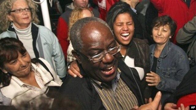 Peter Bossman, center, a Ghana-born physician celebrates his electoral victory in Piran, Slovenia, late Sunday, 24 Oct. 2010