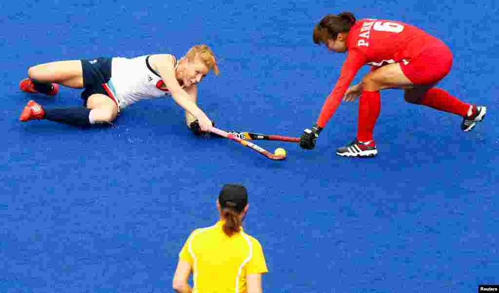 Britain's Nicola White and South Korea's Park Seon-mi fight for the ball during their women's Group A hockey match.
