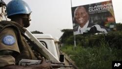Un casque bleu devant une affiche d'Alassane Ouattara