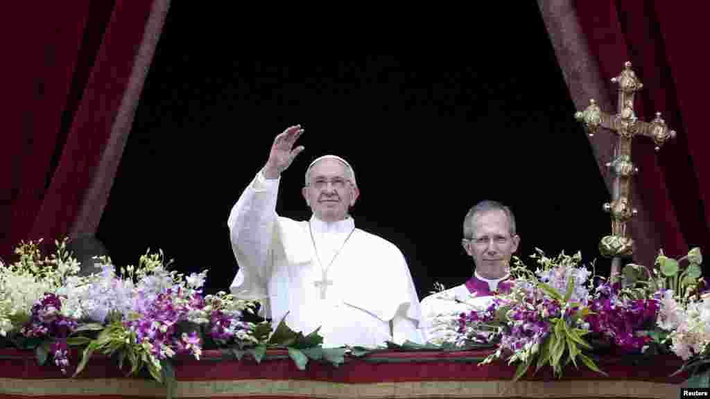 Đức Giáo Hoàng Phanxicô vẫy chào trước khi đọc Thông Điệp Urbi et Orbi Phục Sinh 2015 từ ban công nhìn ra Quảng trường Thánh Phêrô ở Vatican, 5/4/2015.