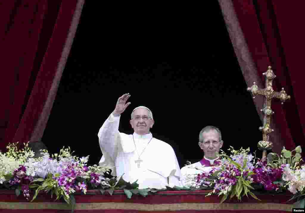 """Paus Fransiskus melambaikan tangannya ketika menyampaikan pesan """"Urbi et Orbi"""" dari balkon yang menghadap ke arah lapangan Santo Petrus di Vatikan, 5 April 2015."""