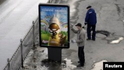 FILE - A worker puts up a billboard showing an image that resembles U.S. President Barack Obama, in Yekaterinburg, Russia, March 31, 2009. A Russian advertising agency has used an image resembling Obama to promote a new vanilla-and-chocolate ice cream.