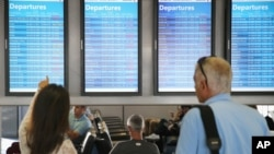 FILE - Passengers check arrival and departure displays at O'Hare International Airport in Chicago, Illinois, Sept. 27, 2014.