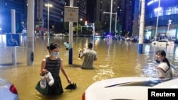 Des personnes pataugent dans l'eau de crue à une intersection après que de fortes pluies ont entraîné des inondations à Hefei, dans la province d'Anhui, en Chine, le 27 juin 2020. Photo prise le 27 juin 2020.