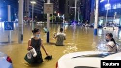 中国安徽合肥的民众在被洪水淹没的街道上过马路。(2020年6月27日)
