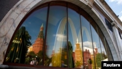 The walls and towers of the Kremlin are reflected in a window of a closed McDonald's restaurant, one of four temporarily closed by the state food safety watchdog, in Moscow, Aug. 21, 2014.
