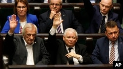 Poland's most powerful politician, ruling Law and Justice Party leader Jaroslaw Kaczynski, center, attends a vote in parliament in Warsaw, Dec. 8, 2017, in which lawmakers approved legislation that gives his party control over the Supreme Court. The oppos