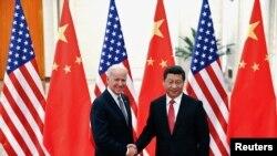 Le président chinois Xi Jinping (à dr.), serrant la main du vice-président américain Joe Biden